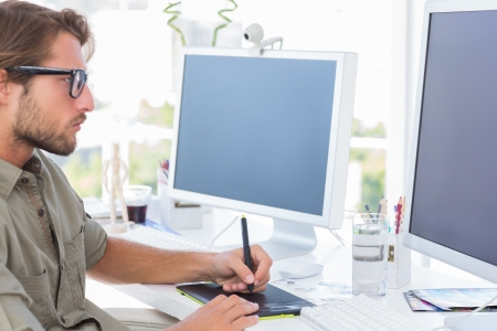 focused: Graphic designer using graphics tablet to do his work at desk Stock Photo
