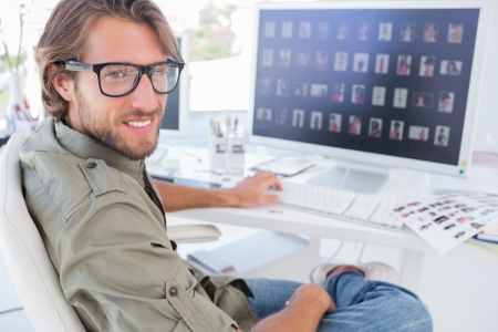 Photo editor turning and smiling at his desk in modern office Stock Photo - 20501583