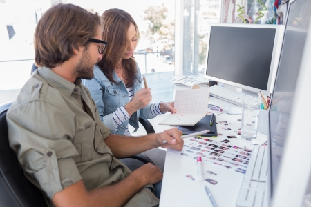 editors: Photo editors working together at desk in bright modern office