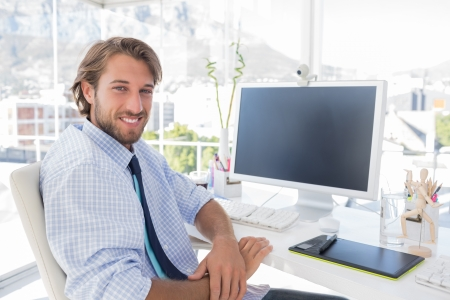 artists mannequin: Smiling designer sitting at his desk in bright modern office