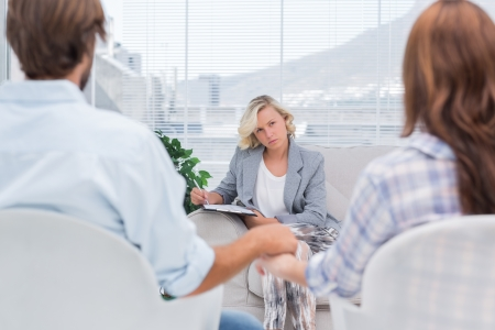 Therapist listening to couple with intent during a session Stock Photo - 20516863