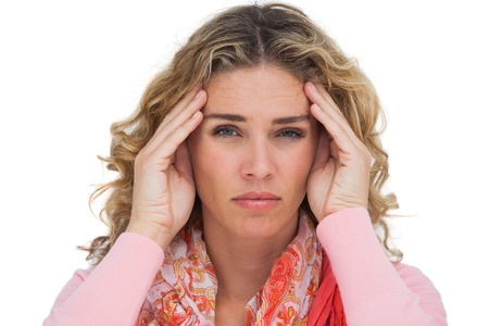 Blonde woman suffering with headache on white background photo