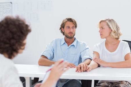 couples therapy: Couple looking doubtful during therapy session as therapist is gesturing at them