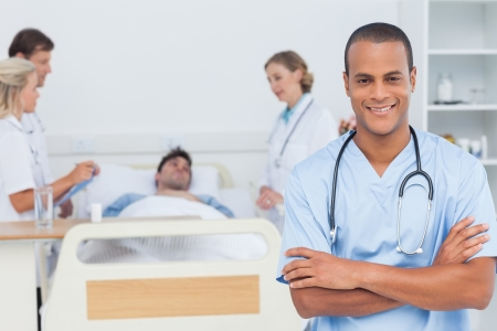 Attractive doctor with arms crossed standing in front of medical team taking care of a patient photo