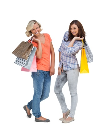 Women doing shopping and holding bags on white background photo