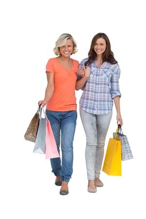 linking together: Two cheerful friends with shopping bags on white background