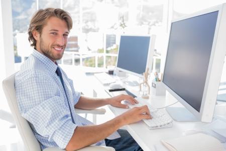 typing man: Smiling designer working at his desk in modern office