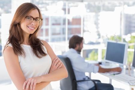 Desginer souriant debout dans son bureau avec des lunettes et un collègue derrière elle