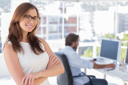 Smiling desginer standing in her office wearing glasses and colleague behind her photo
