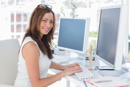 Female designer at her desk smiling at the camera photo
