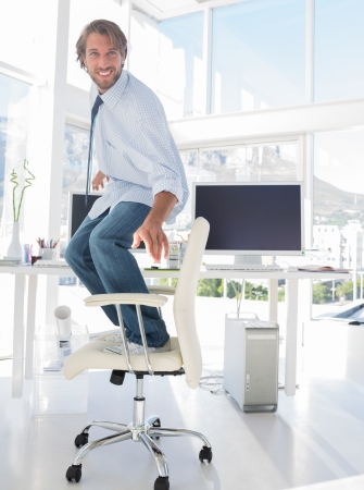 Man surfing his swivel chair in bright modern office photo