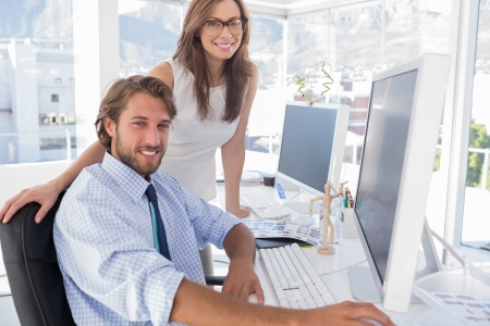 editors: Editors smiling at the camera at their desk in modern office