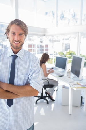 Smiling desginer standing in office with arms crossed and colleague working behind Stock Photo