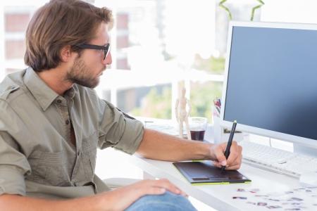 アーティストの机に座ってグラフィック タブレットを使用して
