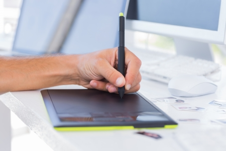 graphics tablet: Male hands using graphics tablet on white desk