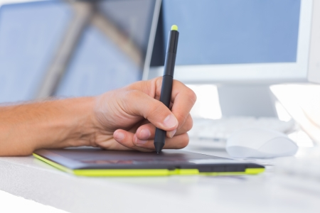 graphics tablet: Male hands using a graphics tablet on a white desk