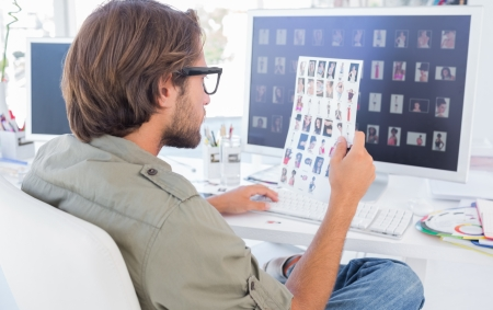 Photo editor examining contact sheet sitting at his desk Stock Photo - 20516889