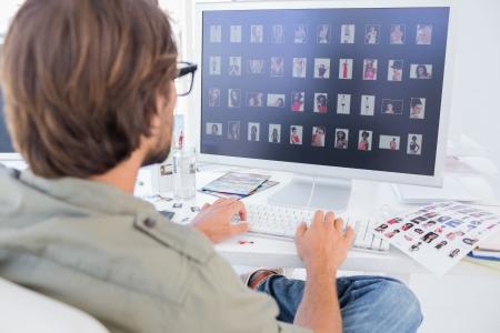 Photo editor viewing thumbnails on computer at his desk Stock Photo - 20501504