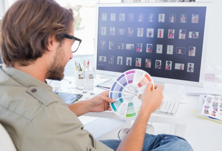 Photo editor looking at colour wheel at his desk Stock Photo - 20501163