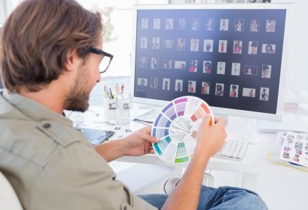 Photo editor looking at colour wheel at his desk Stock Photo - 20501163