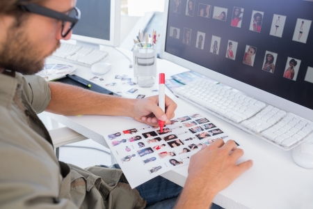 Photo editor marking the contact sheet at his desk in office Stock Photo - 20517034