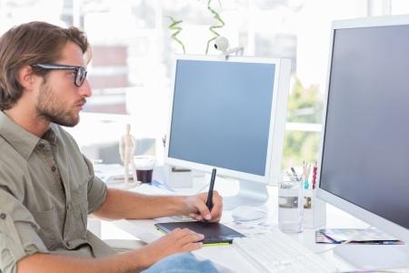 Grafiker mit Grafiktablett an seinem Schreibtisch