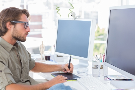 artist: Graphic artist using graphics tablet at his desk