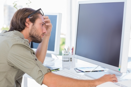 Graphic artist looking at his screen sitting at his desk Stock Photo - 20501240