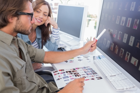 Photo editor pointing at thumbnail on screen with colleague Stock Photo - 20501617