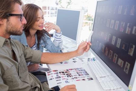 Photo editor pointing at thumbnail on screen with colleague at their desk Stock Photo - 20501554