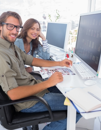 Photo editors smiling at camera sitting at their desk Stock Photo - 20500978