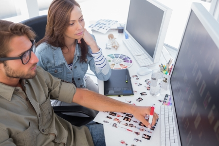 Photo editors choosing thumbnails for final cut at their desk Stock Photo - 20501571