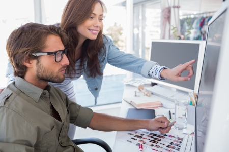 editor: Colleague pointing photo out to editor at desk in office