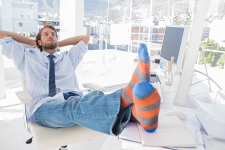 Designer relaxing at desk with no shoes and stripey socks Stock Photo