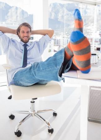 shoeless: Shoeless designer kicking back at his desk and smiling