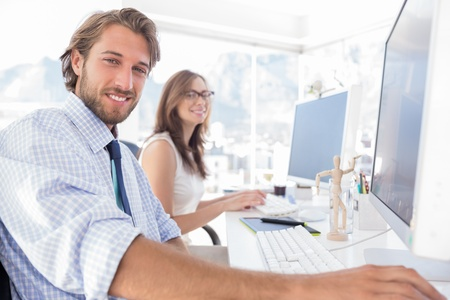 company job: Attractive designers at work at their desk in modern office