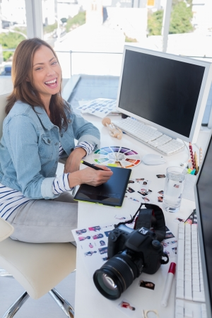 graphic tablet: Laughing photo editor working with a graphic tablet at her desk with camera and contact sheets