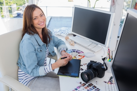 graphic tablet: Cheerful photo editor working with a graphic tablet at her desk with camera and contact sheets