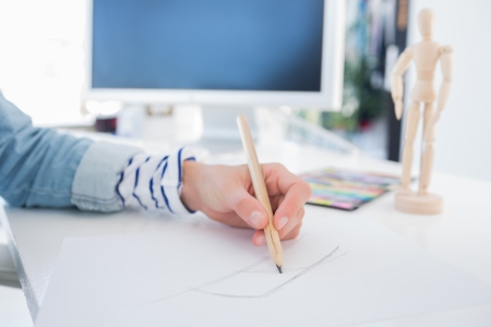 graphic designing: Female hands drawing with pencil on paper on her desk Stock Photo