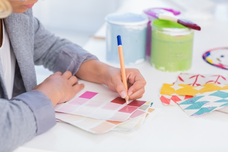 noting: Pretty interior designer drawing on colour samples at her desk with paint pots and colour wheel