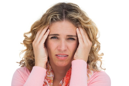 Blonde woman suffering with headache thus touching her temples on white background photo