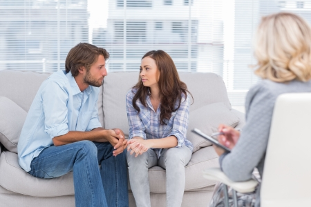 Couple looking to each other during therapy session while therapist watches photo