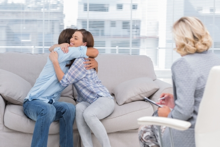 psychotherapy: Young couple cuddling on the couch while therapist watches