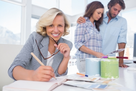 Pretty interior designer sitting at desk with working colleagues behind photo