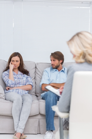Troubled couple sit with arms folded in the office of the therapist photo