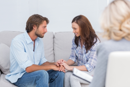 Couple reconciling on the couch while therapist watches photo