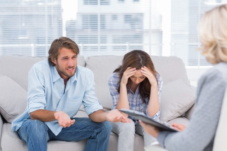 Young couple sit on the couch of the therapist and the woman is crying photo