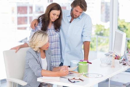 interior designer: United smiling team of interior designer at desk in bright modern office