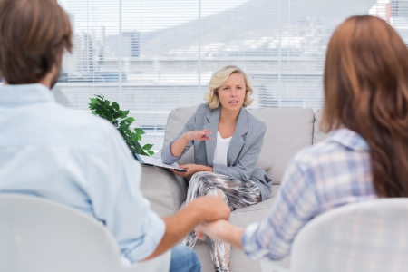 Therapist talking to a couple during a session photo