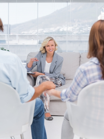 psychotherapy: Smiling therapist speaking a couple during therapy session
